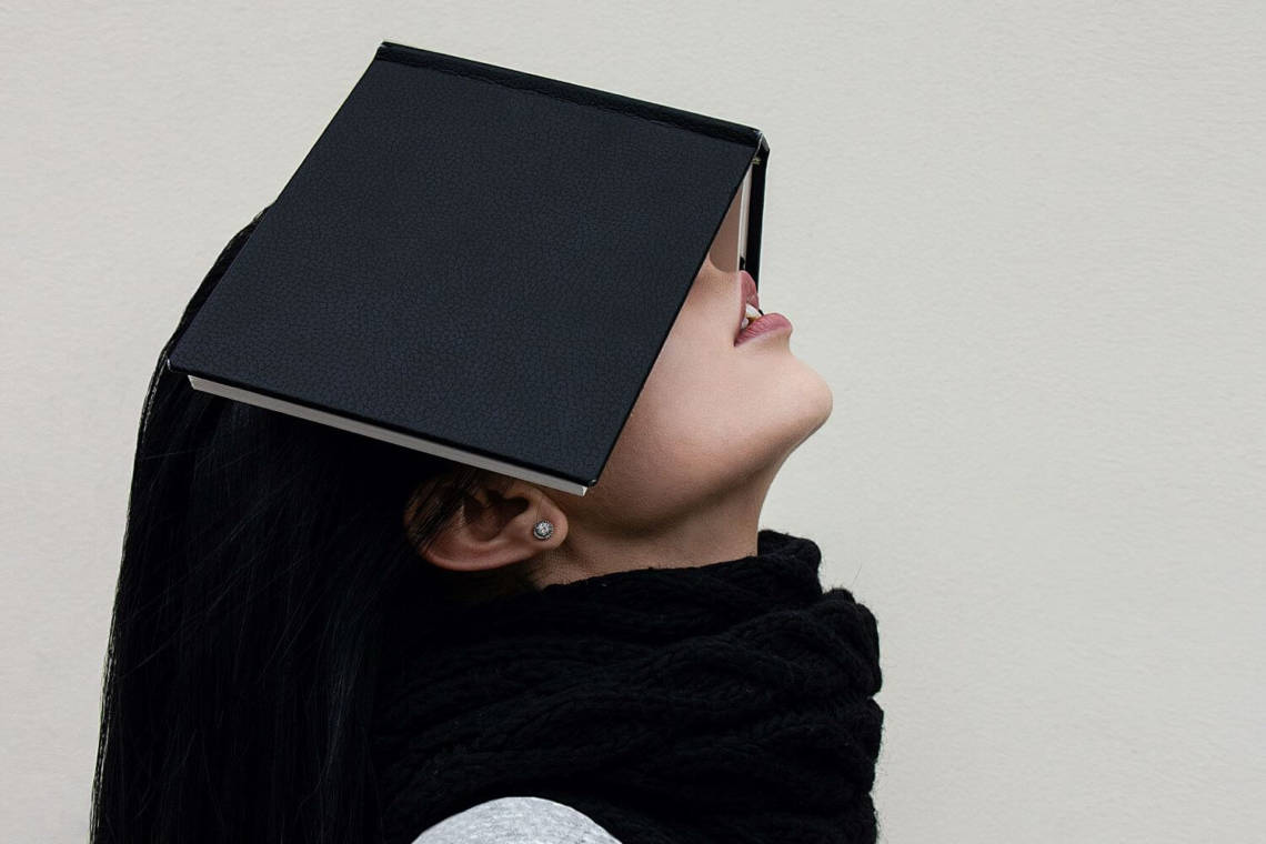 woman with book on her face